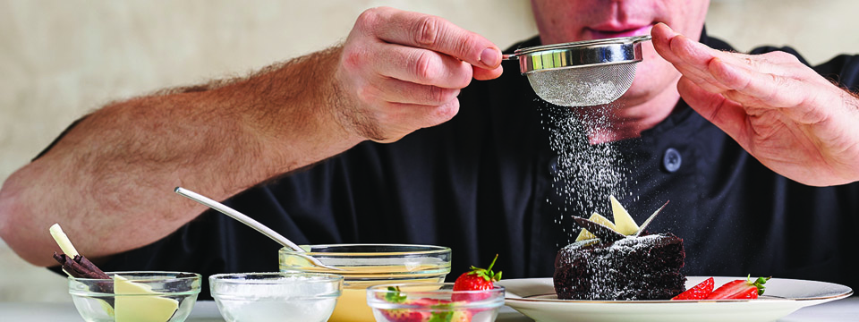 Chef dusting icing sugar on a desert