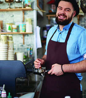 Cheerful barista tamping espresso at coffee shop
