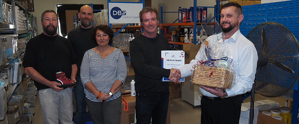 ETC Business Relationship Manager Andrew Goodchild presenting the award to Dale Steedman, also pictured are some of the DBS Medical Supplies staff in their warehouse at the Arts & Industrial estate