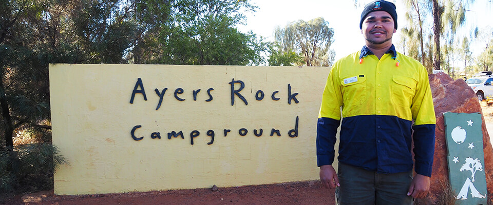 Indigenous job seeker in front of Ayers Rock Campground sign