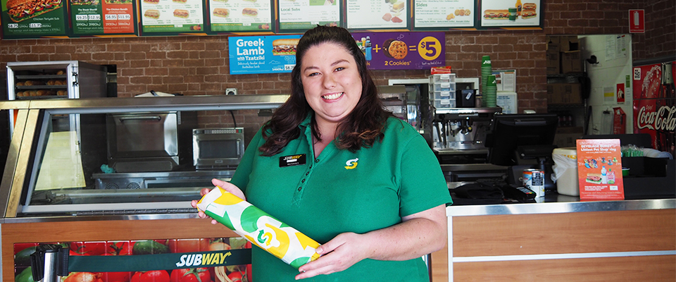 Megan holding a roll standing in subway