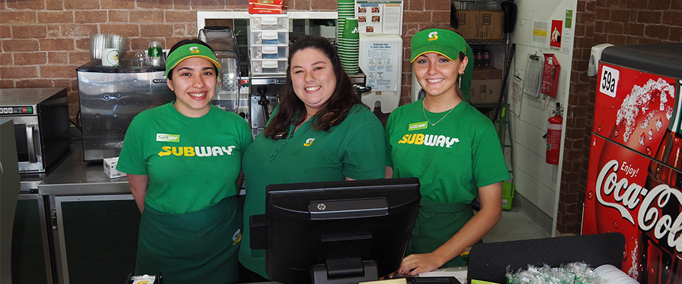 megan standing with her staff at the register