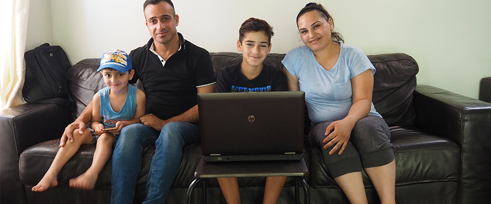 Refugee family receiving new laptop