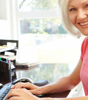 An older woman at computer writing selection criteria