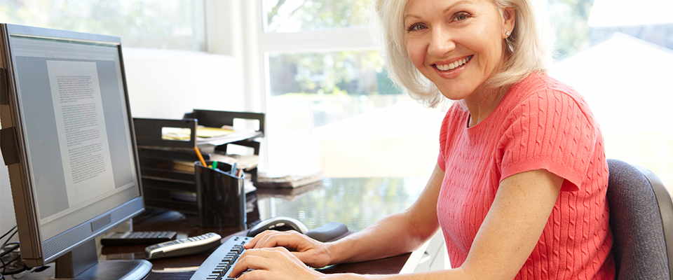 An older woman at computer writing selection criteria